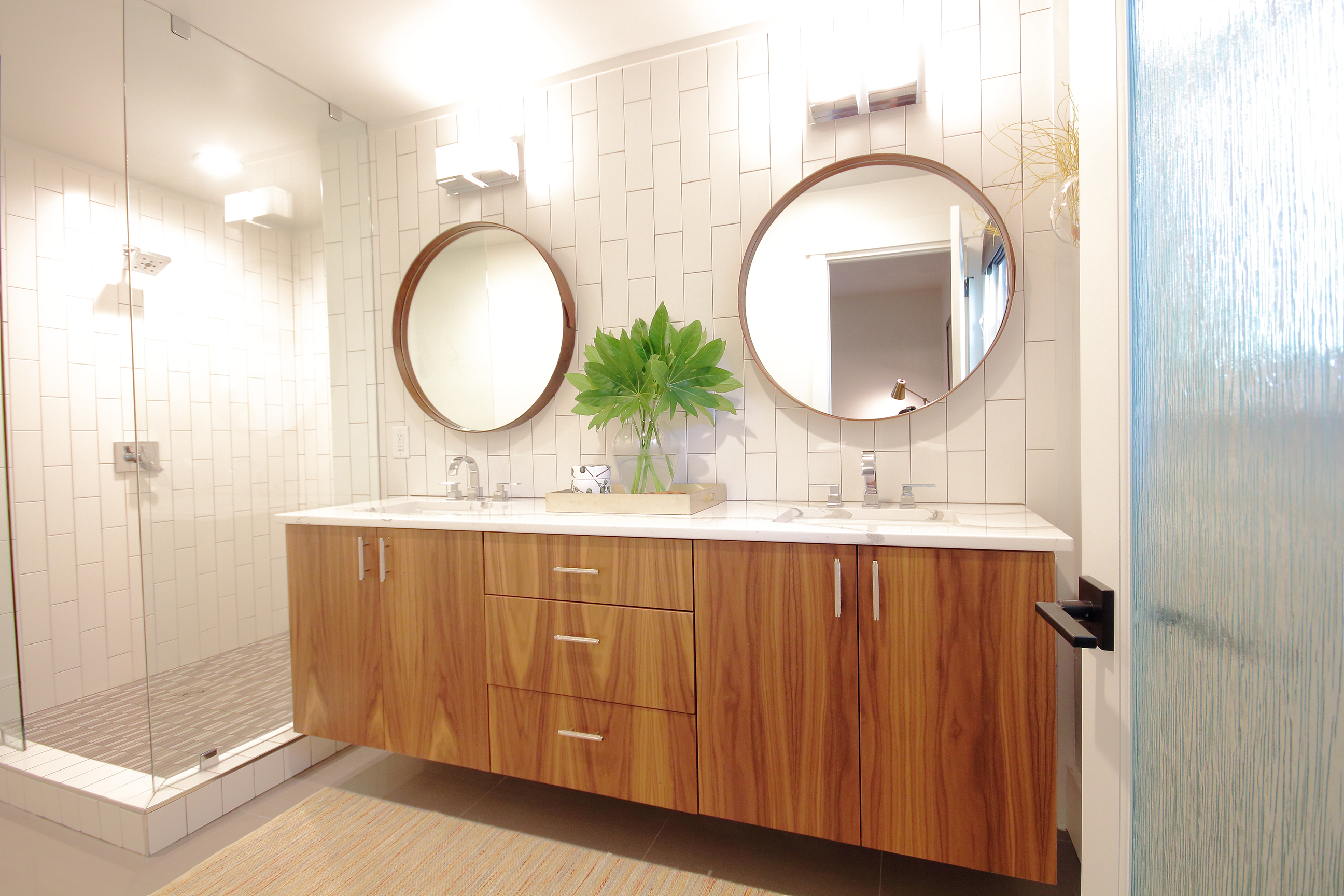 remodeled bathroom with wooden cabinets and circular mirrors