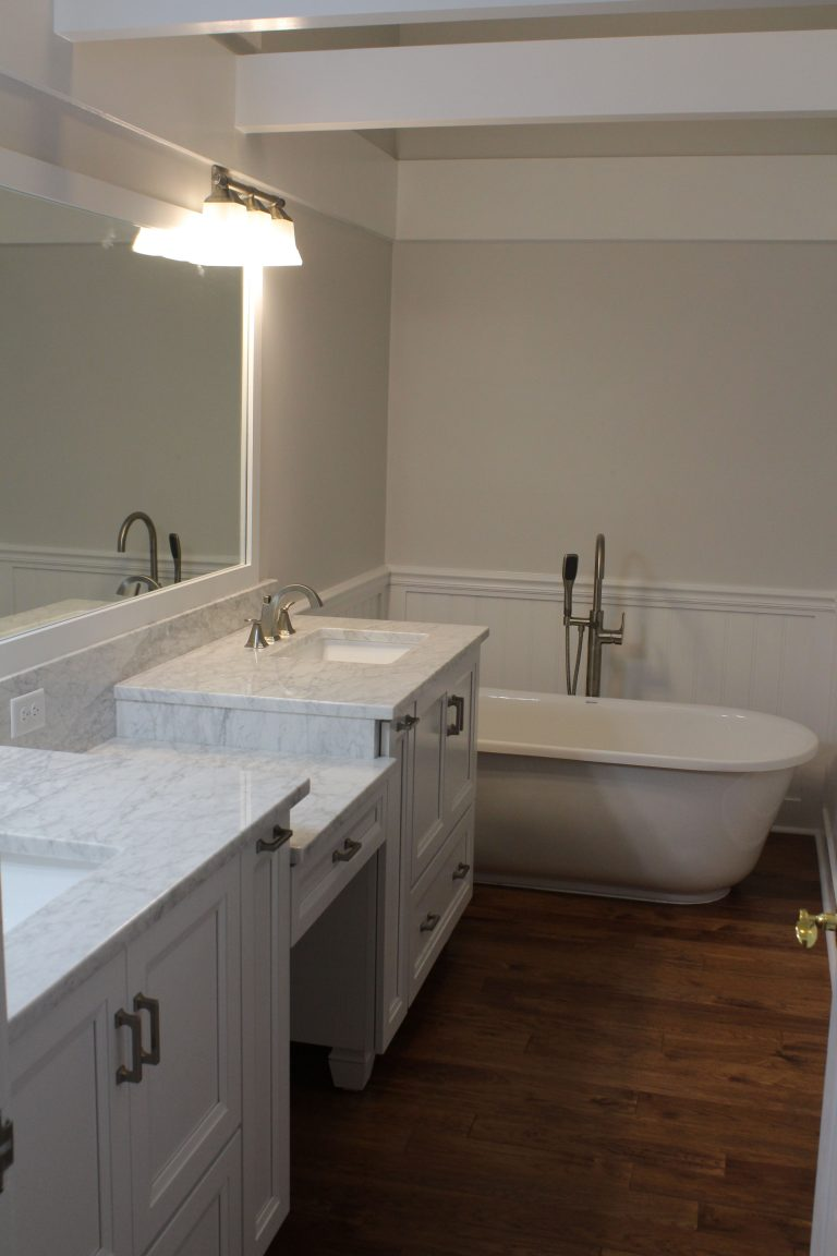 remodeled bathroom with white cabinets and a freestanding bathtub