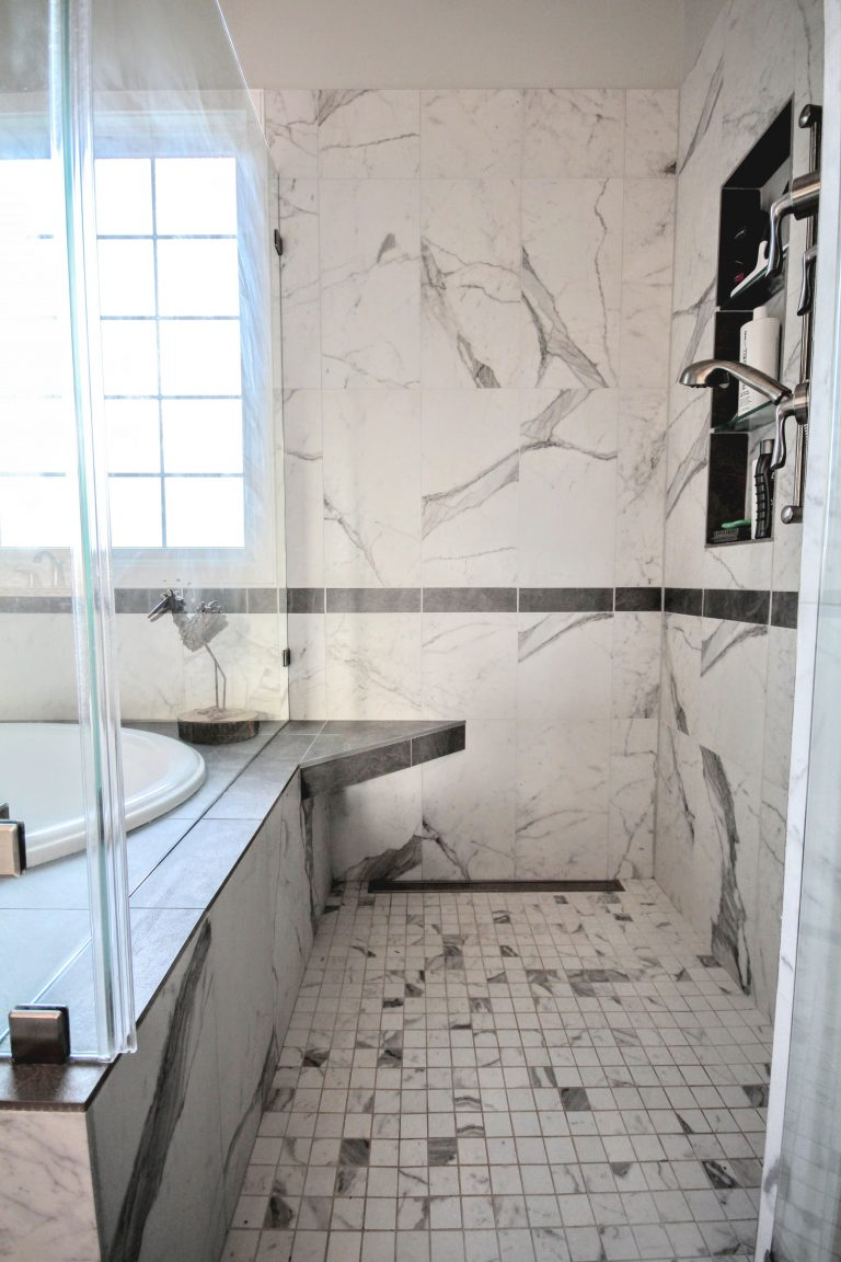 remodeled bathroom with glass bath door with marble walls