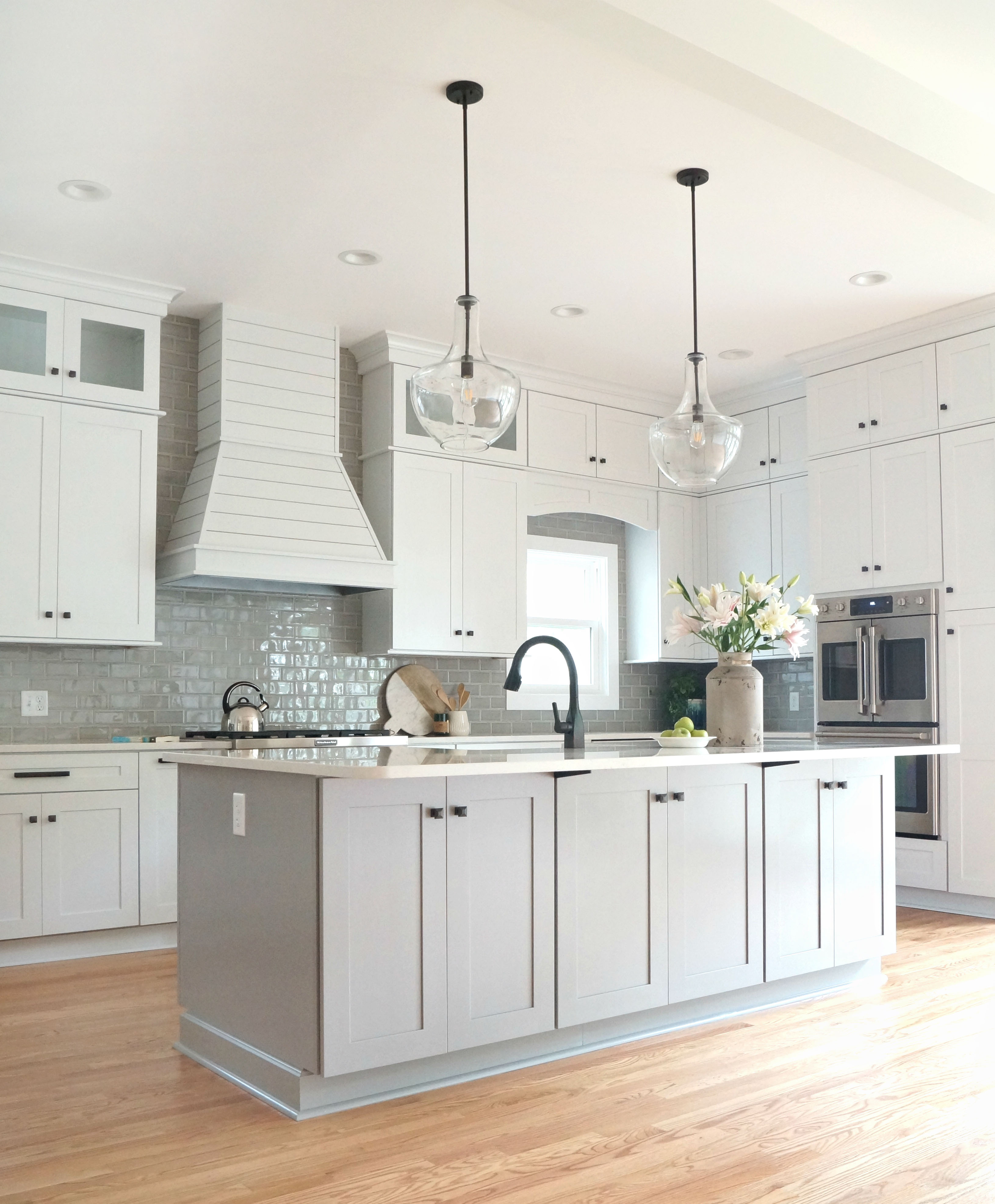 remodeled kitchen with white and gray cabinets and stainless steel appliances