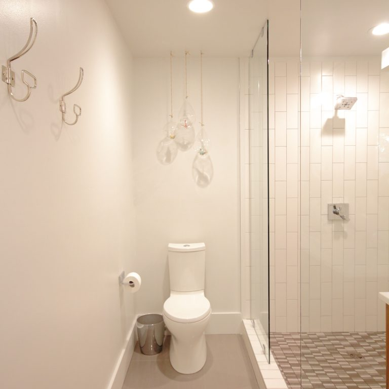 remodeled bathroom with hanging lights and glass shower doors